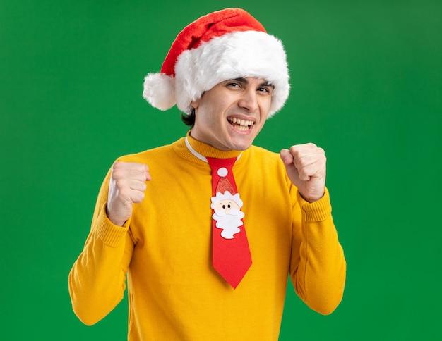 Giovane uomo in dolcevita giallo e cappello della santa con cravatta divertente che guarda l'obbiettivo felice ed emozionato stringendo i pugni in piedi su sfondo verde
