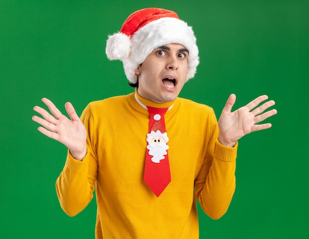 Young man in yellow turtleneck and santa hat with funny tie looking at camera happy and surprised with arms raised standing over green background