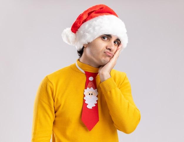 Giovane uomo in dolcevita giallo e cappello santa con cravatta divertente guardando la fotocamera stanco e annoiato in piedi su sfondo bianco