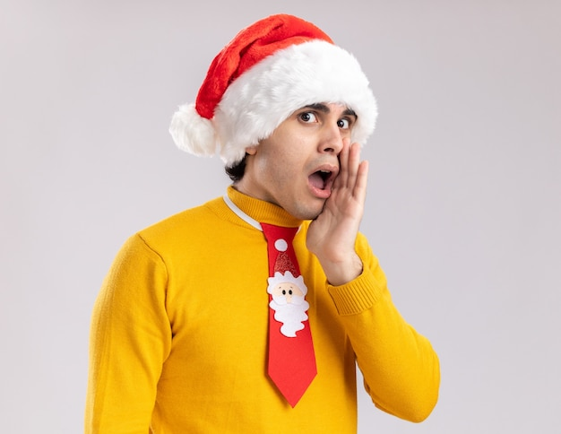 Young man in yellow turtleneck and santa hat with funny tie telling a secret with arm near mouth looking surprised standing over white background