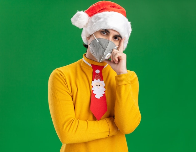 Young man in yellow turtleneck and santa hat with funny tie wearing facial protective mask looking at camera with serious face with hand on chin thinking standing over green background