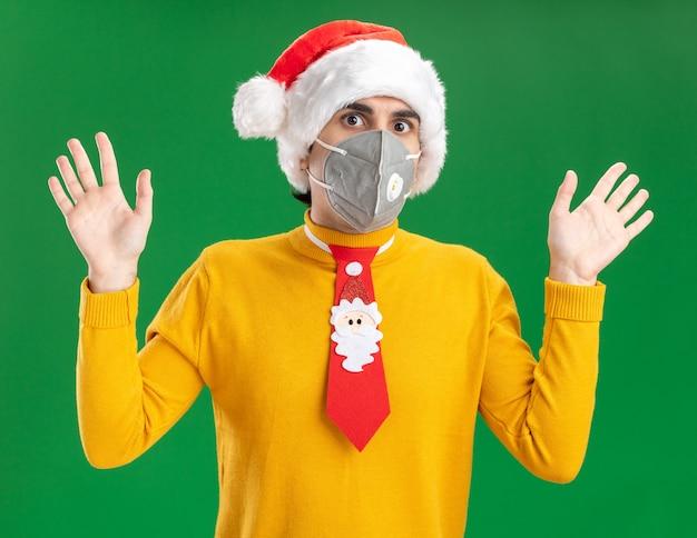 Giovane uomo in dolcevita giallo e cappello santa con cravatta divertente che indossa la maschera protettiva per il viso preoccupato con le braccia alzate in piedi sopra il muro verde