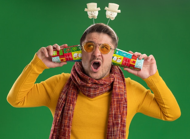 Young man in yellow turtleneck with warm scarf and glasses wearing funny rim on head covering ears with two colorful cups looking up confused with annoyed expression standing over green wall