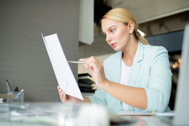 Young manager or banker pointing at financial paper while reading it or checking data by workplace