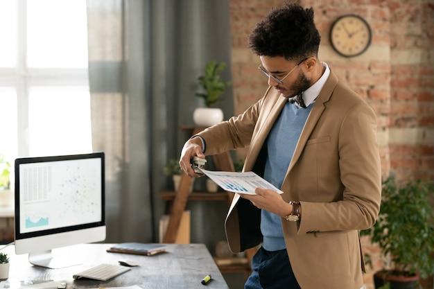 Молодой менеджер в костюме, работающий с финансовыми документами за столом с монитором компьютера в офисе