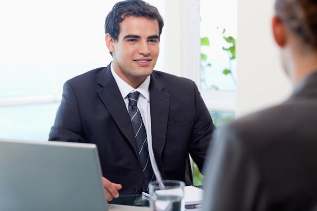 Молодой менеджер беседует с женщиной-заявителем