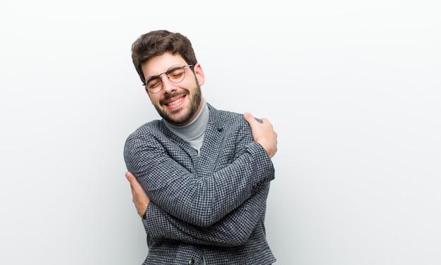 愛を感じて、笑みを浮かべて、抱きしめ、自己を抱きしめ、独身でいて、利己的で、白い壁に対してエゴセントリックである若いマネージャー男