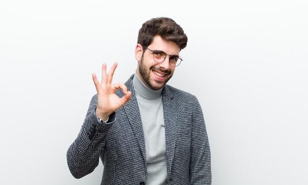 Молодой менеджер человек чувствует себя успешным и довольным, улыбается с широко открытым ртом, делает хорошо знаком со стороны белой стены