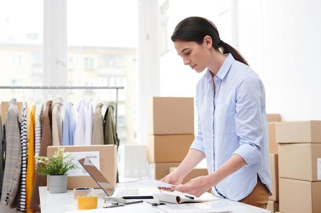 Молодой менеджер интернет-магазина повседневной одежды просматривает буклеты для клиентов перед упаковкой заказов в коробки.