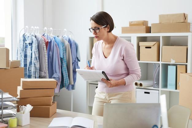 注文の梱包中に商品のリストを作成するオンラインショップの若いマネージャー