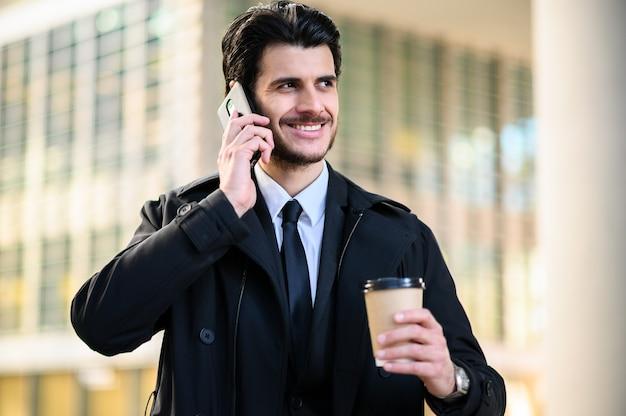 都会の環境で屋外の電話で若いマネージャー