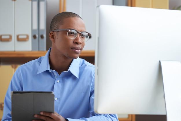 コミュニティの最新のイベントに注目するために、オンラインでビジネスニュースを読む若いマネージャー