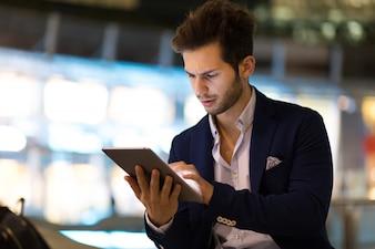夜の現代都市で屋外デジタルタブレットを使用して若いマネージャー
