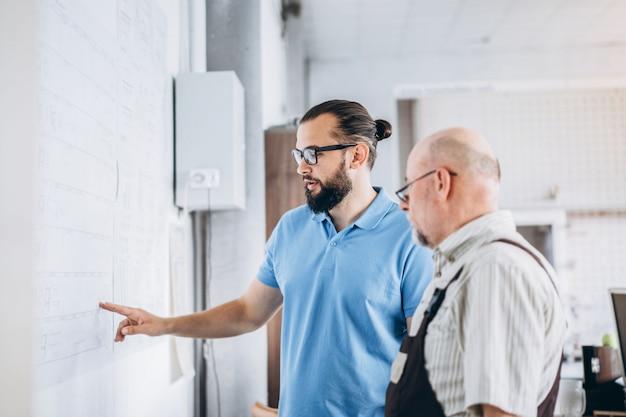 Молодой менеджер с бородой показывая и проверяя рабочий процесс взрослого профессионального работника на большой фабрике.