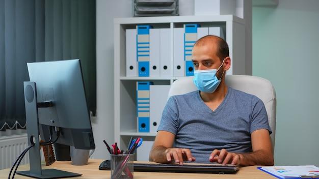 社会的距離の間にオフィスで一人で働いている保護フェイスマスクを持つ若いマネージャー。デスクトップを見てコンピューターのキーボードで新しい通常の個人的な職場の企業の執筆の起業家