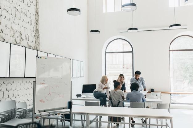 젊은 관리자와 ceo는 아침에 컨퍼런스 홀에서 시간을 보내고 있습니다. 큰 현대 사무실에서 새로운 목표를 논의하는 마케팅 팀의 실내 초상화.