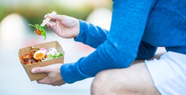Руки молодого человека, держа обед в коробке из переработанной бумаги.