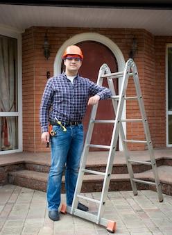 큰 집에 대 한 금속 사다리와 함께 포즈를 취하는 젊은 육체 노동자 프리미엄 사진