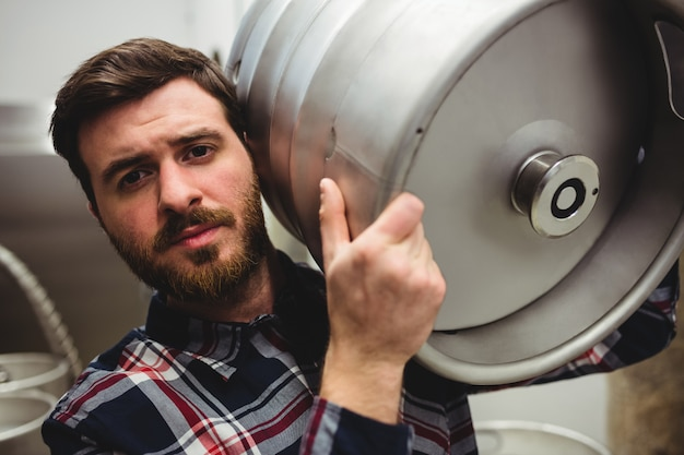 Young manufacturer carrying keg in brewery