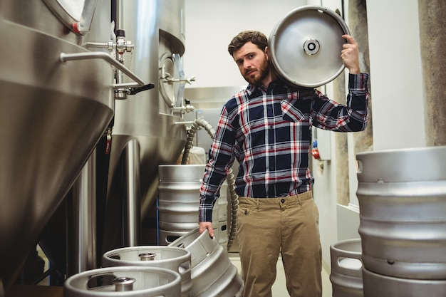 Young manufacturer carrying kegs in brewery