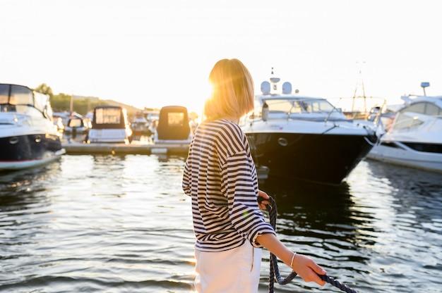 Молодая женщина морского стиля сидит на лодке и смотрит вперед