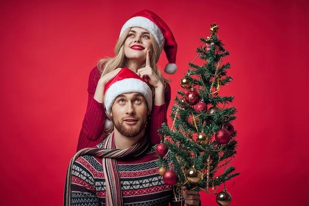 若い夫婦のクリスマスツリーのおもちゃ休日の喜び赤い背景