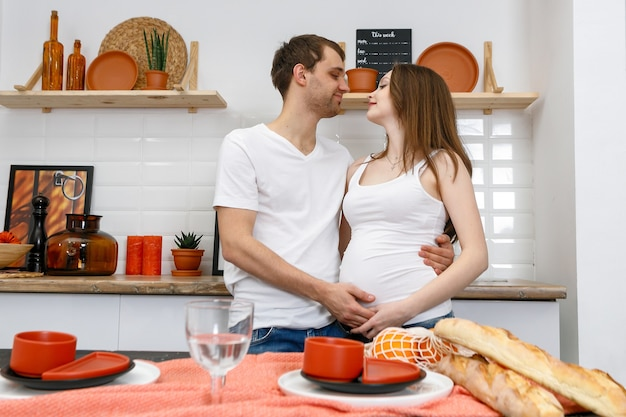 Young married couple embraces standing near table in kitchen. husband hugs his pregnant wife, putting his hands on her big belly. a loving couple, future parents. lifestyle, happy people.