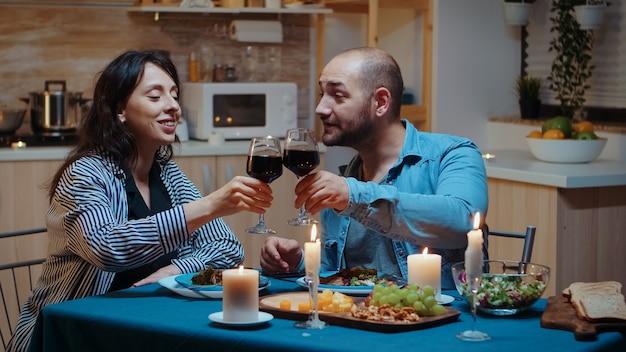 젊은 부부는 아늑한 주방에 있는 테이블에 앉아 낭만적인 저녁 식사를 즐기고 레드 와인을 마시고 있습니다. 촛불에서 기념일을 축하하는 식사를 함께 하는 행복한 어른들