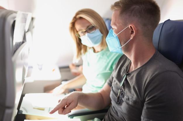 保護用医療マスクを着用して飛行機で飛んでいる若い夫婦。 covid19パンデミックコンセプト時の旅客輸送規則