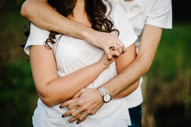 젊은 부부 포옹, 남편과 아내가 자연에 손을 잡고. 하반부. 확대. 손 맹세, 빈티지 스타일. 손에 집중하십시오. 사랑의 여름.