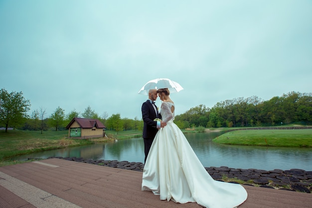 Young married couple hugging under the umbrella in raining weather
