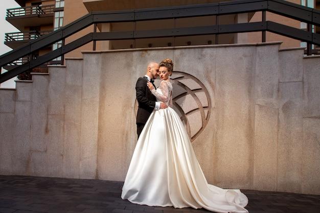 屋外で抱き締めるエレガントなスーツを着た若い夫婦