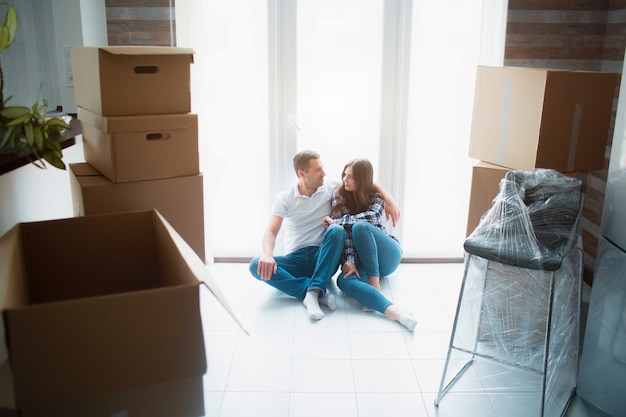A young married couple in the living room in the house are sitting near the window. they are happy about new home. moving, buying a house, apartment concept.