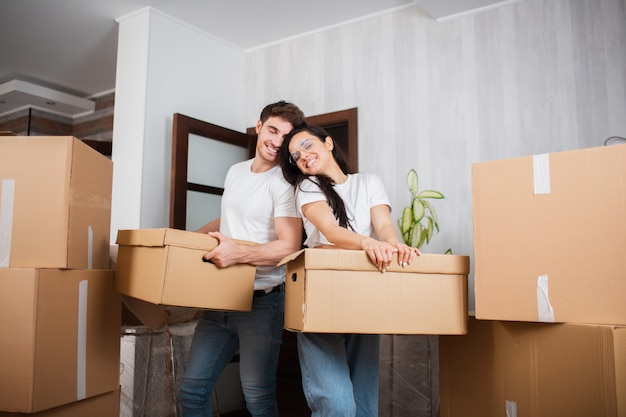 Young married couple in the living room in the house stand near unpacked boxes. they are happy about new home. moving, buying a house, apartment concept.