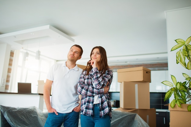 A young married couple in the living room in the house stand near unpacked boxes.