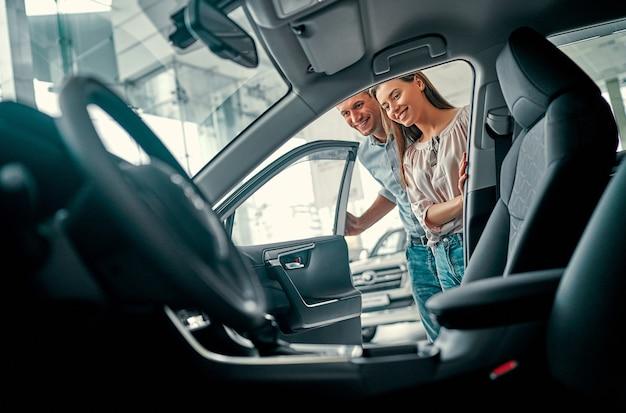 Молодая супружеская пара заглядывает в машину в автосалоне. покупка и аренда авто.