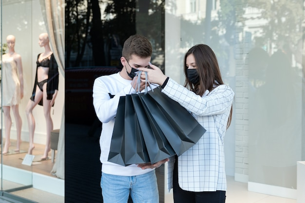 Young married couple in medical masks holds black bags on shop windows background. sale.