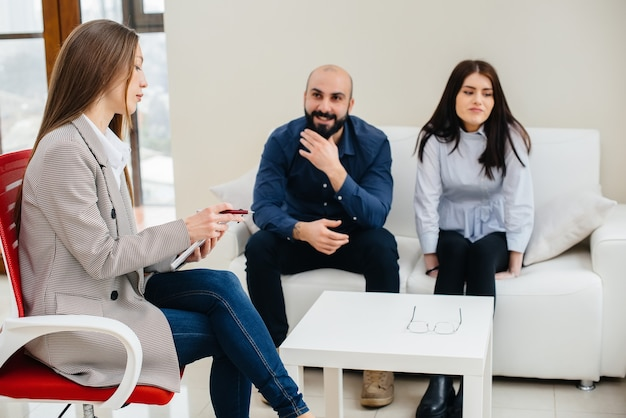 A young married couple of men and women talk to a psychologist at a therapy session. psychology.