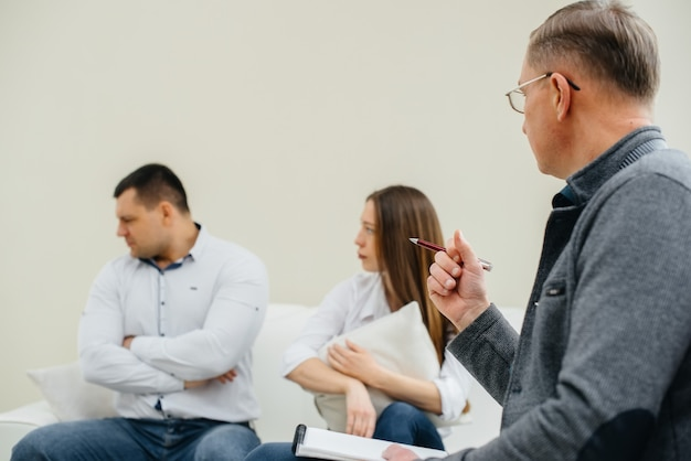 A young married couple of men and women talk to a psychologist at a therapy session