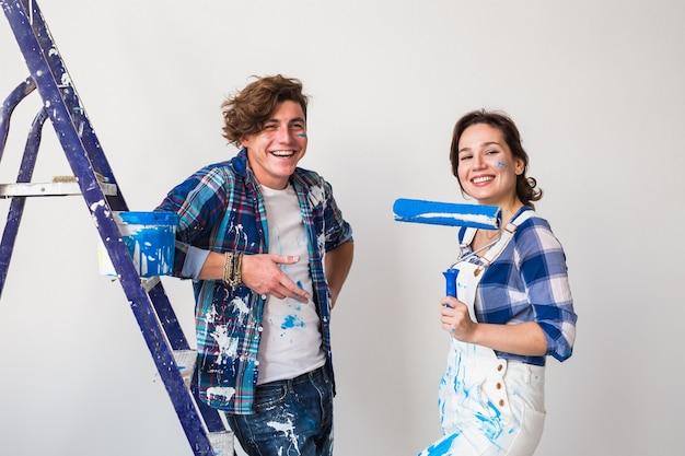 彼らの新しい家で壁を塗っている若い夫婦。