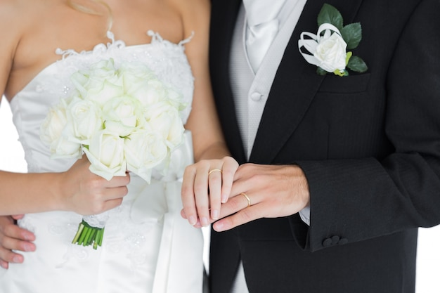 Young married couple posing holding hands