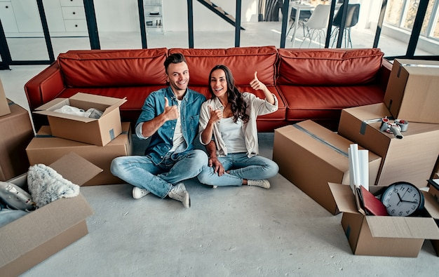 Young married couple show thumb up in living room at house. smiling happy wife and husband relaxing resting unopened belongings still in their cardboard boxes. moving and relocate new home concept.
