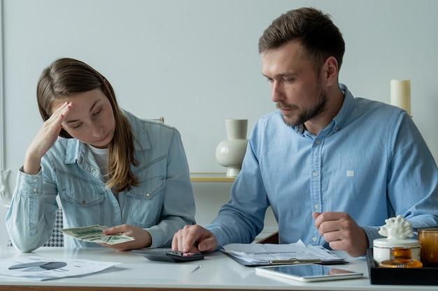 Молодая супружеская пара, сидящая за столом в гостиной, изучает документы, делает расчеты на калькуляторе, изучает семейный бюджет