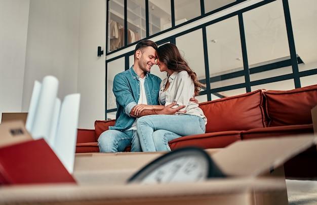 집에 있는 거실에서 껴안고 있는 소파에 앉아 있는 젊은 부부. 행복한 남편과 아내는 즐거운 시간을 보내고 있으며 새로운 가정을 기대하고 있습니다. 이사, 집 구입, 아파트 개념.