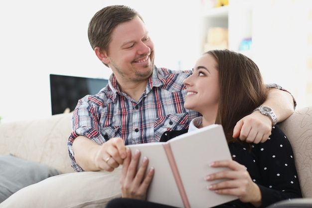 젊은 부부는 책을 들고 소파에 앉아 서로를 바라보고 있습니다. 가족 개념의 낭만적 인 관계