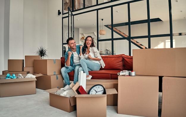 집에 있는 거실에 있는 소파에 앉아 있는 젊은 부부. 행복한 남편과 아내는 즐거운 시간을 보내고 있으며 새로운 가정을 기대하고 있습니다. 새로운 집 개념을 이동하고 재배치합니다.