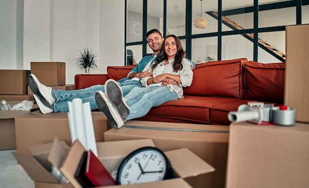 Young married couple sitting on the sofa in the living room at home. happy husband and wife are having fun, are looking forward to a new home. moving, buying a house, apartment concept.
