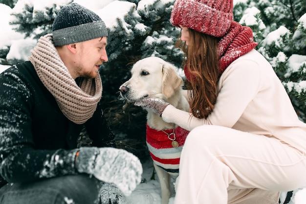 Молодая супружеская пара гладит свою собаку на заснеженной улице, сидя рядом с ней