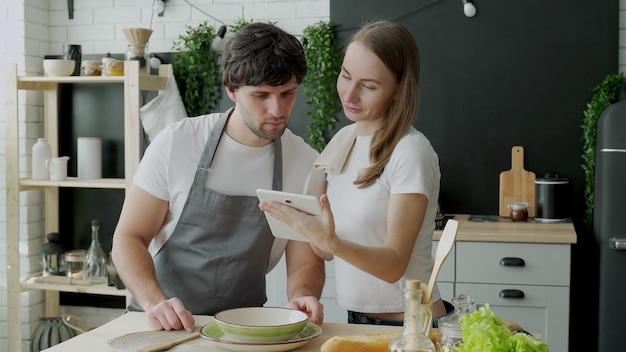 若い夫婦はデジタルタブレットを使用して、自宅のキッチンで料理をしながら笑顔