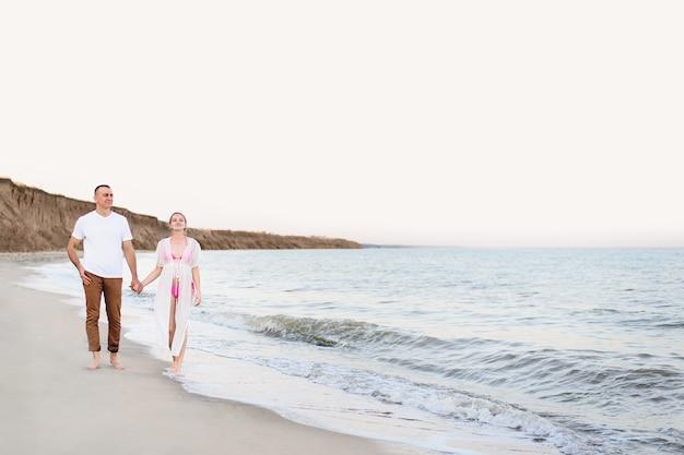 Молодая супружеская пара гуляет по берегу моря